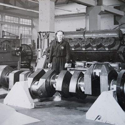 Herr Georg Hadolt hat uns dieses Foto aus den Jenbacher Werken zugesandt. Er schreibt dazu Folgendes:  Hier sieht man im Hintergrund das Modell LM 1500 und im Vordergrund steht eine Kurbelwelle vom VM6 1500 SGO Verdichter Bj 70- 77. Das Jahr ist leider nicht bekannt.